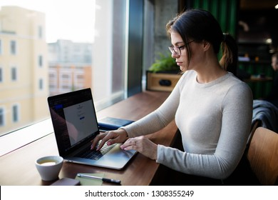 Serious woman in stylish casual wear and spectacles professional business content writer searching information in internet via pc laptop computer, sitting in coffee shop. Hipster girl using apps