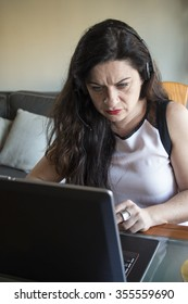 Serious woman working on laptop at home office desktop