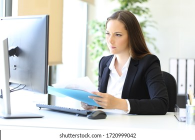 Serious worker checking online information comparring it with paper documents at office