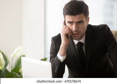 Serious worried businessman talking on cellphone in office with thoughtful confused expression, discussing solving problem, contacting customer service, receiving bad news, having tough mobile talk