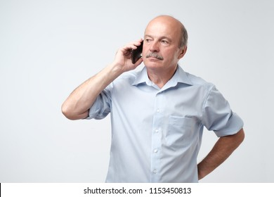 Serious, worried, upset mature man talking on cellphone. An old employee deciding some problems over telephone.