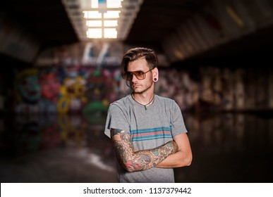 Serious young adult tattooed man under the bridge , subculture concept