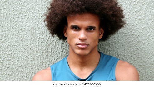Serious Young african mixed race man leaning on wall staring camera with arms crossed
