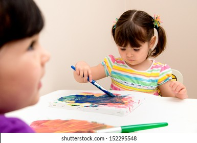 Serious young artist focused on her painting as her sister watches