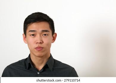 Serious young Asian man looking at camera.