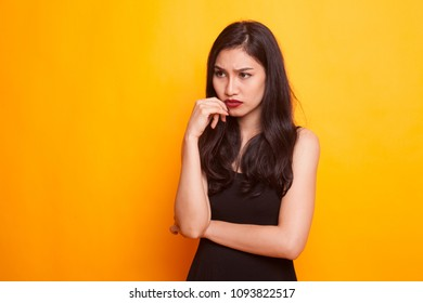 Serious  young Asian woman  look away on yellow background