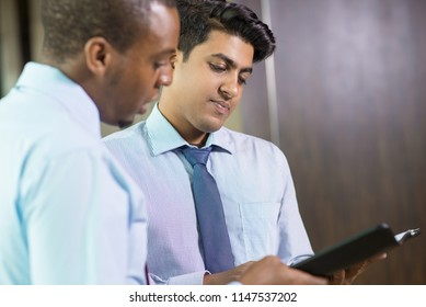 Serious young attorneys reading case details. Multi-ethnic business team working with documents at meeting. Financial report concept