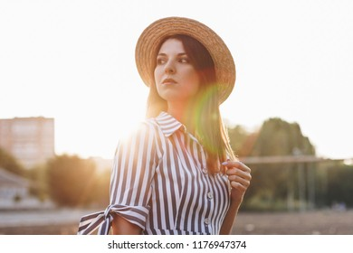 serious young attractive woman wearing striped dress and straw hat