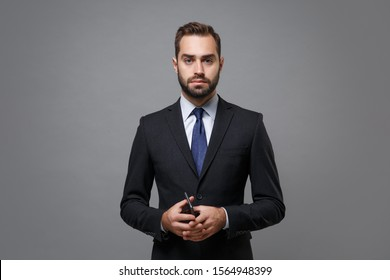 Serious young bearded business man in classic suit shirt tie posing isolated on grey background studio portrait. Achievement career wealth business concept. Mock up copy space. Holding mobile phone