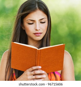 serious young, beautiful girl holding an open book, read background summer green park