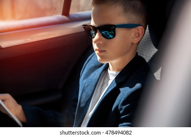 serious young boy in sunglasses sits on a backseat of a car