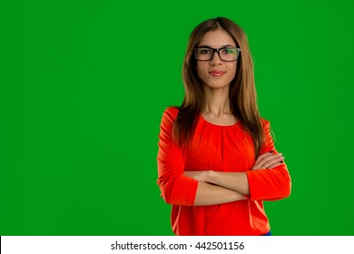 Serious young brunette in glasses looking at the camera isolated on green screen