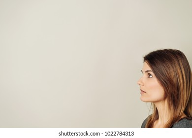 Serious young brunette woman in the corner of the frame looking up at blank copy space on a neutral background