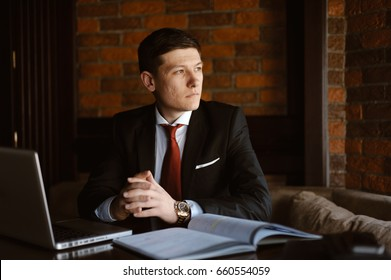 Serious young business man sitting in restaurant at his laptop and looking somewhere.