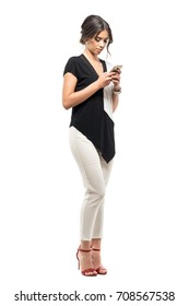 Serious young business woman in black and white suit reading message on the cellphone. Full body length portrait isolated on white studio background.