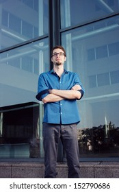 serious young businessman with arms crossed in front of workplace