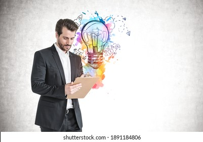 Serious young businessman with clipboard standing near concrete wall with colorful business idea sketch drawn on it. Mock up