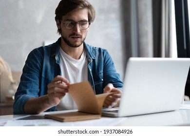 Serious young businessman with the glasses sitting and using laptop at home office and taking notes.