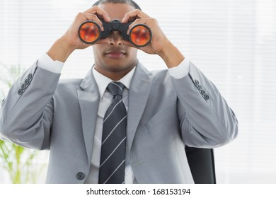 Serious young businessman looking through binoculars in office