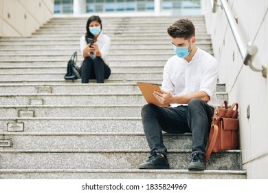 Serious young businessman in medical mask reading report on tablet computer, his colleagues working in background