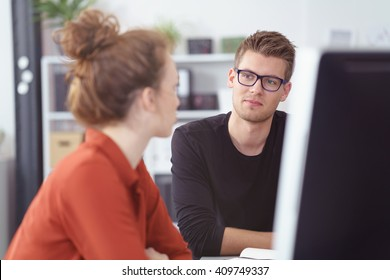 Serious young businessman in a meeting listening to a female colleague with a thoughtful expression