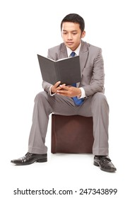 serious young businessman reading a book, isolated on white background