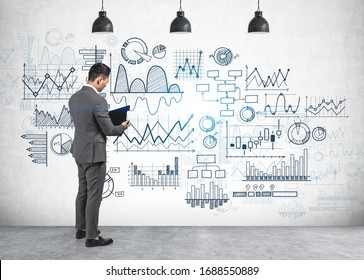 Serious young businessman reading financial report standing near concrete wall with types of graphs drawn on it. Concept of statistics and market analysis
