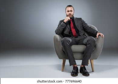 Serious young businessman sitting in armchair with hand to chin and looking to camera, isolated on gray