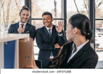 Serious young businesswoman holding folder while colleagues standing and looking behind