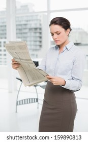 Serious young businesswoman reading newspaper in a bright office