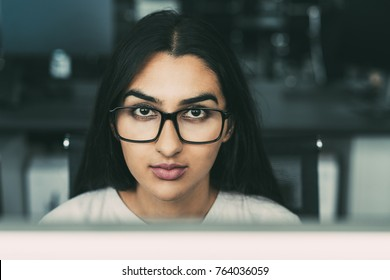 Serious young businesswoman sitting at laptop