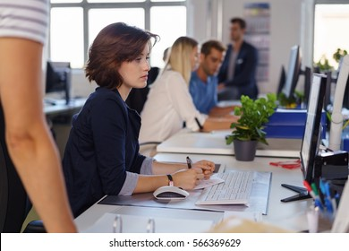 Serious young businesswoman working at her desk at a large desktop monitor watched by a colleague in a busy open plan office