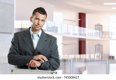 Serious, young caucasian businessman checking time at business center. Standing, looking at camera, suit and tie, suitcase, copyspace.