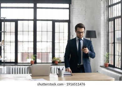 Serious young Caucasian businessman in suit stand near office desk look at cellphone screen consult client online. Focused male CEO or boss use modern smartphone gadget for business negotiation.