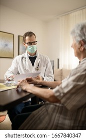 Serious young Caucasian doctor wearing safety mask consulting and advising senior white-haired woman during house call medical visit