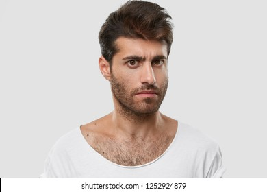Serious young Caucasian man with dark thick stubble, trendy haircut, casual clothes, models against white background, frowns eyebrows, being angry with someone. Masculinity and lifestyle concept