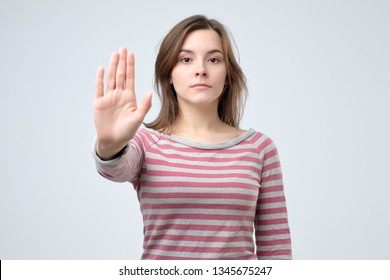 Serious young caucasian woman showing stop gesture with her hand.