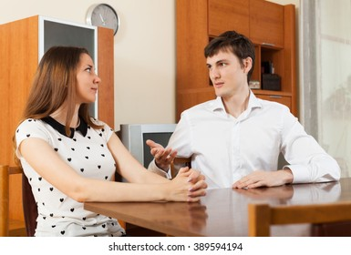 Serious young couple talking  in living room