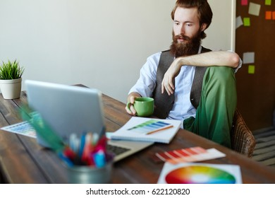 Serious young designer looking at laptop display by workplace