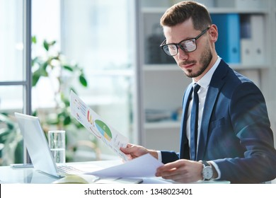 Serious young economist in eyeglasses and formalwear looking through financial papers by workplace