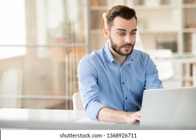 Serious young employee looking at laptop display while sitting by desk and analyzing online data