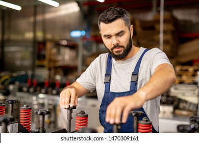 Serious young factory worker setting industrial machine in workshop