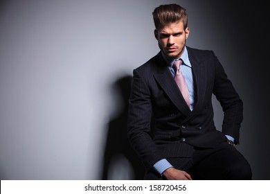 serious young fashion business man in classic suit and tie is sitting on a chair and looking at the camera on gray background