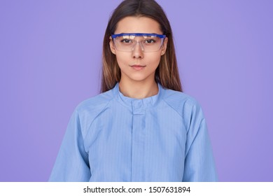 Serious young female in lab safety goggles and blue coat looking at camera during work against violet background