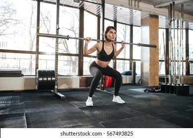Serious young fitness woman doing squats exercises in gym