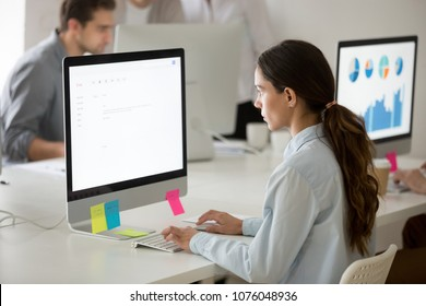 Serious young girl intern focused on writing email working on computer, young female office employee or trainee apprentice using pc mail software for corporate clients communication or support
