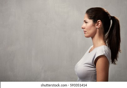 Serious young girl profile over gray wall background