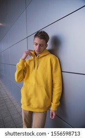 A serious young guy in a yellow hoodie, a cute stylish fashion man in bright clothes against a gray wall