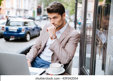 Serious young handsome businessman holding cup of coffee and working with laptop in cafe outdoors