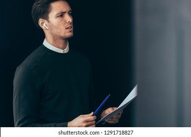 Serious young handsome man have a conversation with colleagues during meeting with wireless earphones. Caucasian businessman using wireless headphones in business conference making notes on paper.